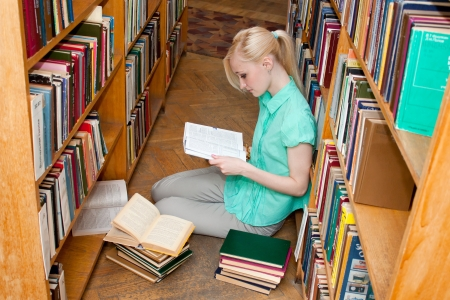 Female university student reads a book in the library photo