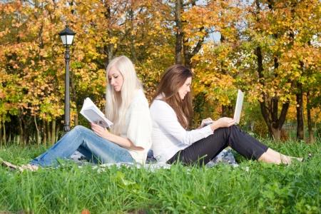 Girls study in autumn park photo