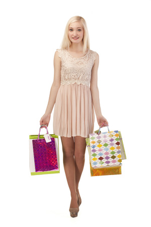Beautiful young woman posing with shopping bags, isolated on white background photo