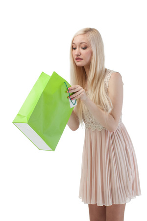 Woman looking to shopping bag, isolated on white background photo
