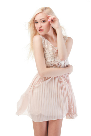 Sexy blonde woman posing with wind in the hair and dress, isolated on white background photo