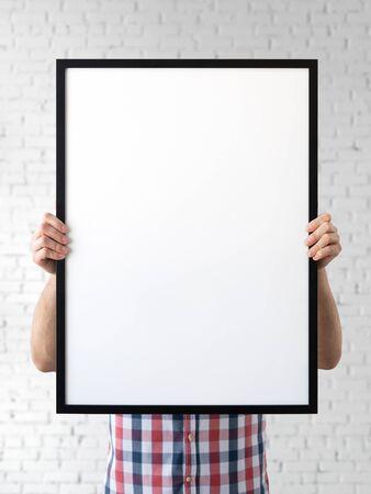 Holding frame mockup. Photo Mockup. The man hold frame. For frames and posters design. Foto de archivo - 133315831