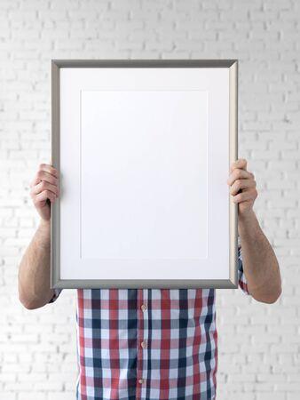 Holding frame mockup. Photo Mockup. The man hold frame. For frames and posters design. Foto de archivo - 133315834