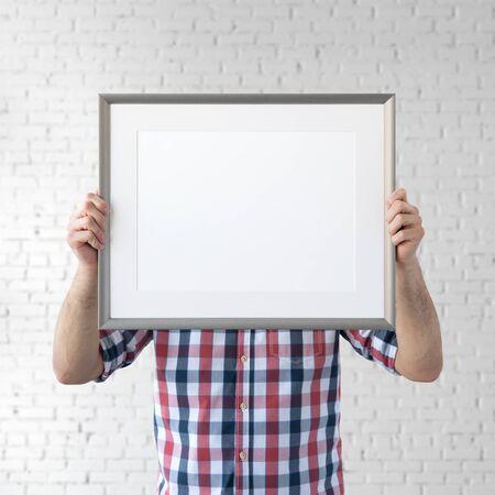 Holding frame mockup. Photo Mockup. The man hold frame. For frames and posters design. Foto de archivo - 133315840