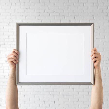 Holding frame mockup. Photo Mockup. The man hold frame. For frames and posters design. Foto de archivo - 133315839