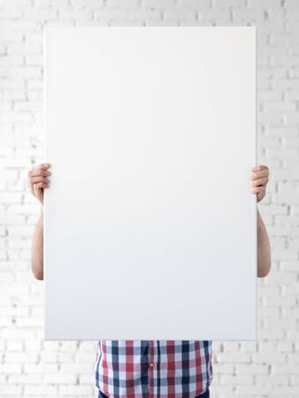 Holding canvas mockup. Photo Mockup. The man hold canvas. For frames and posters design.