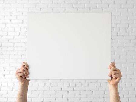 Holding canvas mockup. Photo Mockup. The man hold canvas. For frames and posters design. Reklamní fotografie