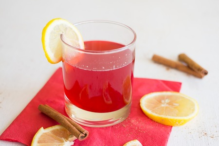 cranberry juice: Cranberry juice with lemon and cinnamon on a red napkin