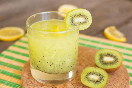kiwis: Glass of kiwi juice with fresh kiwis on wooden table Stock Photo