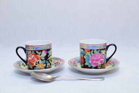 Mock-up / Design-Set aus eleganter und traditioneller bunter Kaffeetasse und Teetasse auf dem Teller der Tasse, Trinkgeschirr, Küche isoliert auf weißem Hintergrund