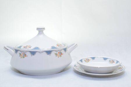 Mock-up / Design-Set aus eleganter und traditioneller Teekanne, bunter weißer und blauer Kaffeetasse und Teetasse auf dem Tassenteller neben der heißen Teekanne, Design / Trinkgeschirr / Serviergeschirr / Suppe isoliert auf weißem Hintergrund Standard-Bild
