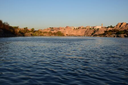 River Nile/ beautiful view for Aswan Egypt and Nubian Egyptian culture. sailing boat sailing in the River Nile and harbor with birds and local houses on the 2 sides