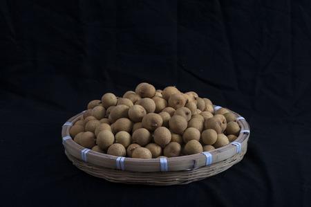 Longan fruit in een bamboe mand geïsoleerd op zwarte achtergrond