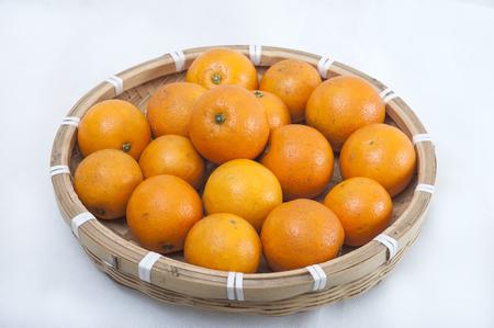 Oranje in een bamboe mand geïsoleerd op een witte achtergrond