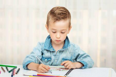 Cute boy doing homework writing and painting. Children paint Фото со стока