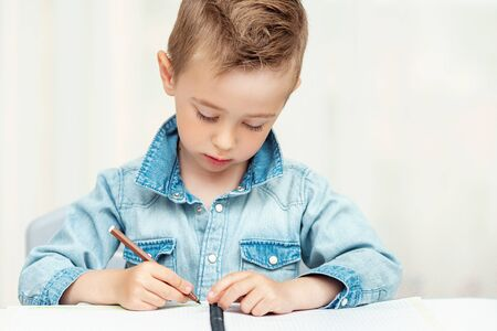 Portrait of child boy drawing with colorful pencils Фото со стока