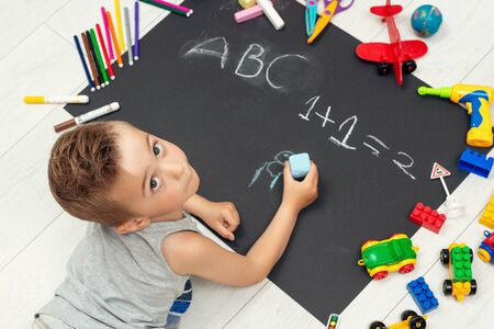 Little boy drawing with chalk on black paper