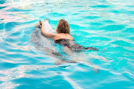 Girl swims in pool with dolphin. Girl swims holding on to dolphin Imagens