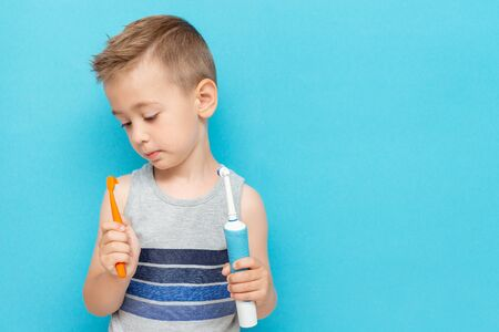 Little boy chooses between electric and conventional toothbrushes