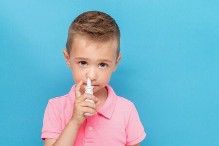 Portrait of a kid with anti-allergic nosal spray on a blue background