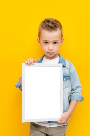 Serious kid holding white frame with copy space for text certificate or diploma