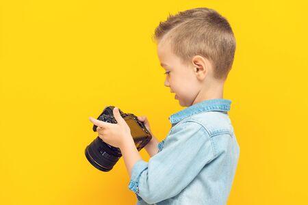 Adorable little boy studies the digital camera