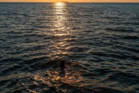 A girl disappearing in a wave in a refreshing sea, ocean, on a hot summer day in the rays of the sunset. solar reflexes on the water
