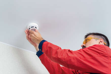 Worker installing fire alarm or smoke detector on the ceiling