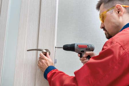 Worker installing or repairing the doorknob with screwdriver