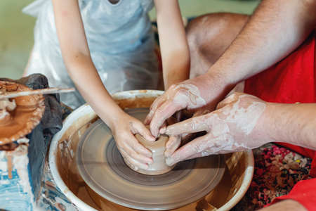 Potter teaches a little boy how make clay pot. Close-up of hands working on pottery wheel.