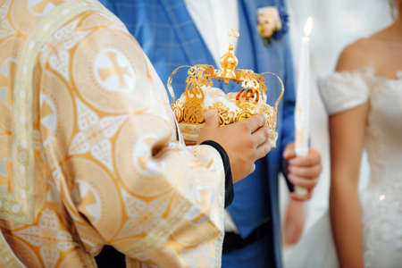 Close up of cristian priest hands with crown for wedding