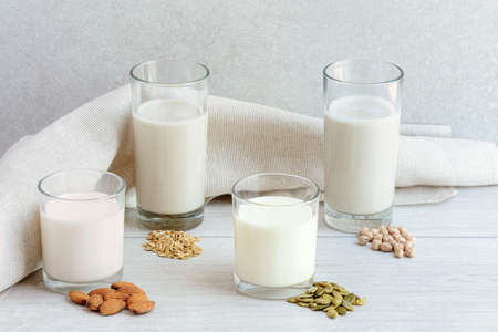 Four different glasses of vegan non dairy milk from nuts, seeds, cereals and legumes. Assortment of organic vegan milk