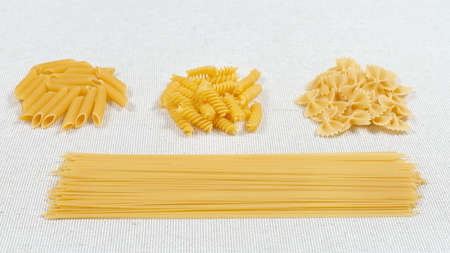 Various pasta on a fabric background. Assorted raw pasta. Gluten free food.
