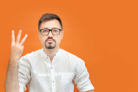 Handsome serious confident business man wearing nerd glasses over orange background showing and pointing up with fingers number three. Archivio Fotografico