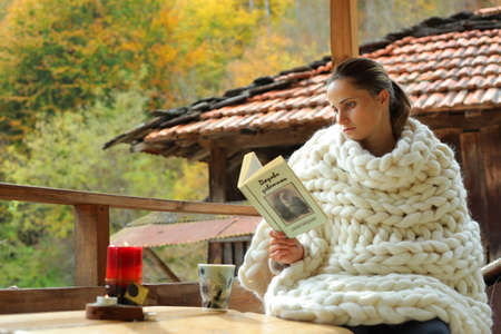 A young woman reading a book. She is cover in a woollen blanket. It's a rural scene in a village.