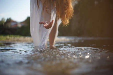 A girl/ young woman with red hair and a white dress. She is playing with water. The photo is taken in a rural scene. The weather is sunny, yet the light is soft and warm.