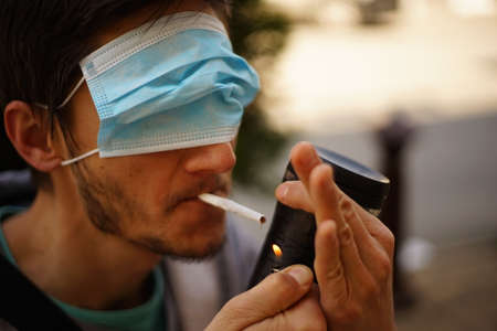 A portrait of a man with a face mask on his eyes. He is lighting a cigarette. Stock fotó