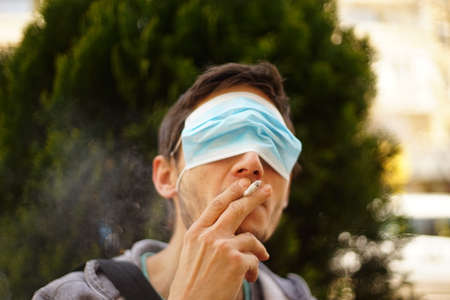A portrait of a man with a face mask on his eyes. He is smoking a cigarette. Stock fotó
