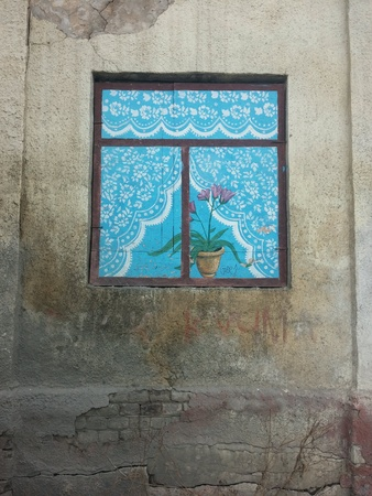 Painted window on the wall of ruined house