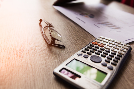 calculator and glass on table, Concept business and financial Stock Photo