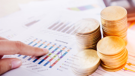 speculation: Concept of currency trading. Stack of coins and a hand holding is examining a technical chart of financial instrument. making a decision for an optimal gain. Business and finance concept.