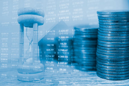 fv: Concept idea Time of money.Stack of coins and a clock hands. Money is a major factor in the current lifestyle.Concept about currency market or foreign exchange.Stack of coins of financial investment Stock Photo