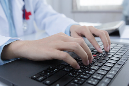 doctoral: Healthcare business and doctorate education concept : Male doctor working on desk with laptop computer in office for medical data record of doctoral analysis. Stock Photo