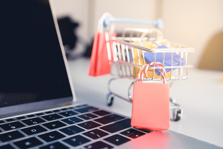 Shoping online concept, Colorful paper shopping bag in trolley on laptop. Customer can buy everthing from office or home and the messenger will deliver.