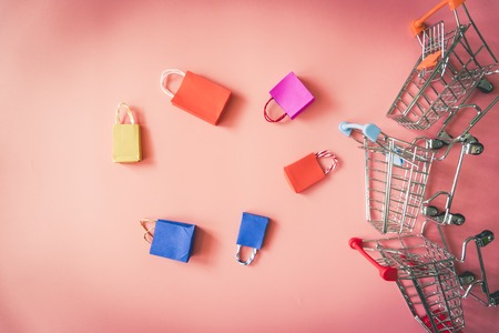 Minimal shoping online concept, Colorful paper shopping bag and trolley go down from floating pink background for copy space. Customer can buy everthing form home and the messenger will deliver. Stock Photo
