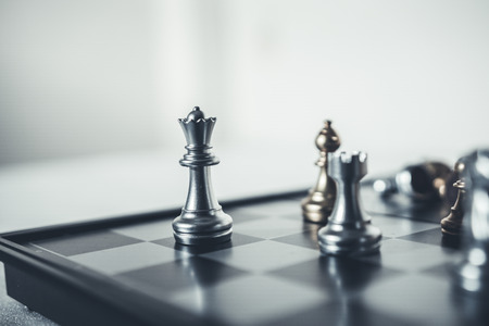 Investment Leadership Concept : The king chess piece with chess others nearby go down from floating board game concept of business ideas and competition and strategy plan success meaning.
