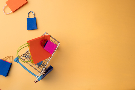 Minimal shoping online concept, Colorful paper shopping bag and trolley go down from floating yellow background for copy space. Customer can buy everthing form home and the messenger will deliver.
