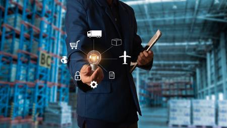 Concept de logistique d'entreprise, gestionnaire d'homme d'affaires touchant l'icône pour la logistique sur fond d'entrepôt de commerce moderne. Concept de l'industrie 4.0 Banque d'images