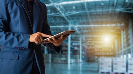 Concepto de logística y transporte: Gerente de empresario mediante verificación y control de tableta y planificación para la logística del almacén de comercio moderno. Foto de archivo