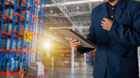 Gerente de empresario mediante verificación y control de tableta para trabajadores con logística de almacén de comercio moderno. Concepto de industria 4.0